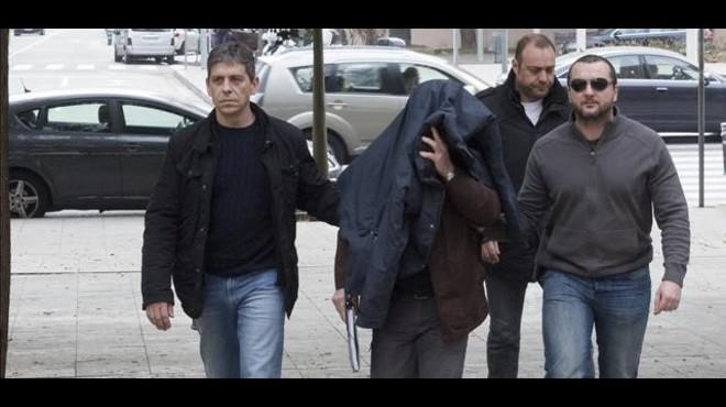 Joaquim Benítez, con la cabeza cubierta, se dirige al juzgado para prestar declaración, rodeado de agentes de los Mossos d'Esquadra.