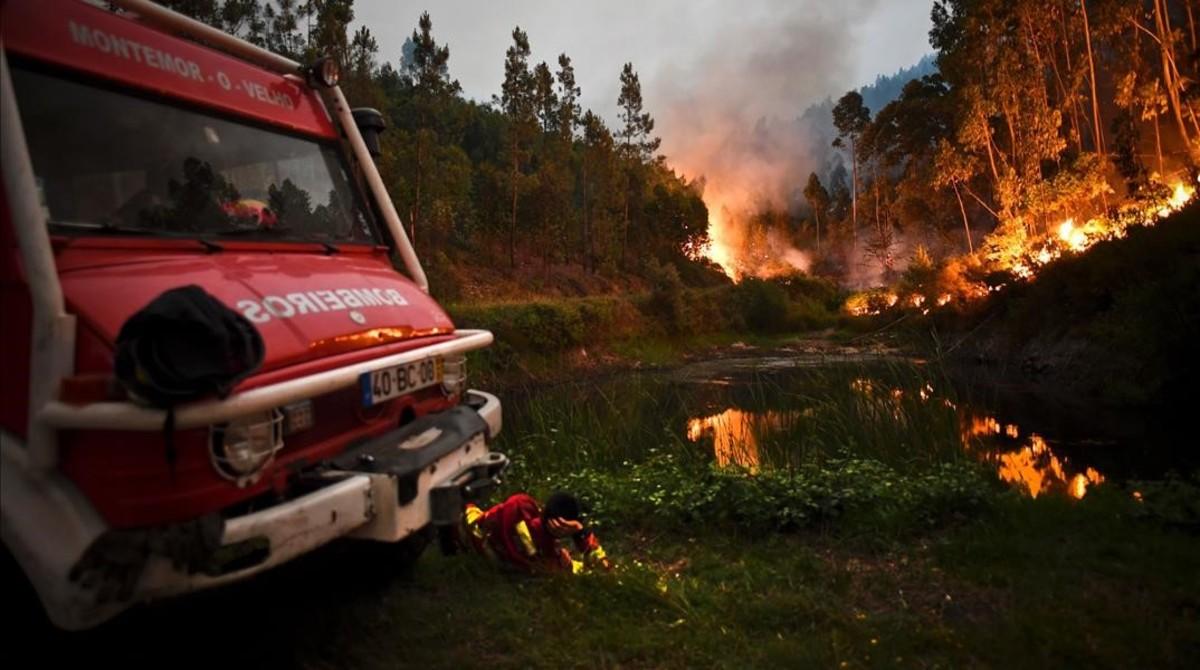 zentauroepp38938879 a firefighter rests next to fire combat truck during a wildf170618090335