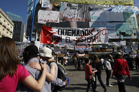 Los carteles de los indignados solapan la valla gigante de un anuncio de Paz Vega.