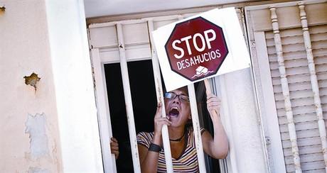 Una dona protesta des de la finestra d'una casa durant un acte de desnonament, el juny del 2011, a Madrid.