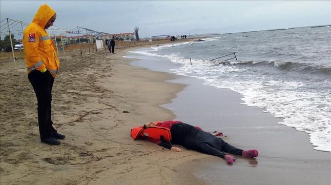 Un miembro de los equipos de rescate contempla el cuerpo de un inmigrante sobre la playa en Ayvalink (Turquía).