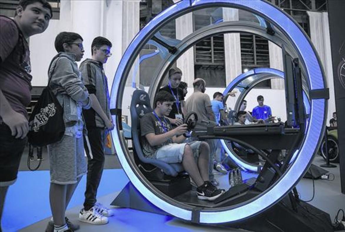Varios jóvenes asistentes a la Barcelona Games World prueban uno de los juegos presentados en la feria.