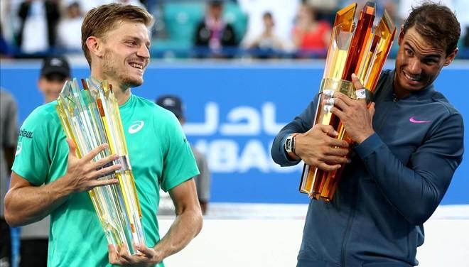 Goffin y Nadal muestran sus trofeos tras la final de Abu Dabi, ganada por el mallorquín.