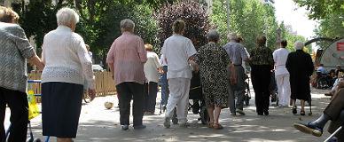 Un grupo de ancianos pasea con sus cuidadores por el paseo de Sant Joan de Barcelona.