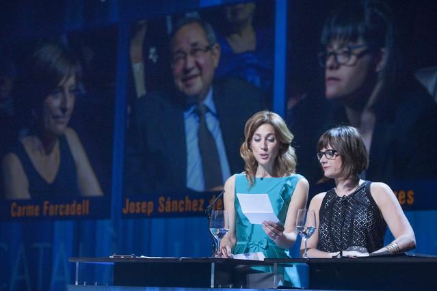 Las presentadoras de la gala del Català de l'Any, Helena Garcia Melero y Ariadna Oltra, con los tres finalistas en una pantalla detrás.
