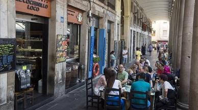 Una de las pocas terrazas que quedanen los porches del mercado de la Boqueria, mientras en el resto del tramo, al fondo,se han tenido que retirar lasmesas por falta de acuerdo con el ayuntamiento.