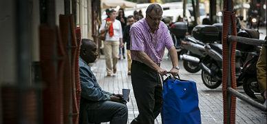 Un hombre pide limosna a la puerta de un supermercado de Barcelona.