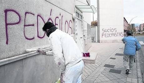 Un operario borra pintadas contra los acusados en la parroquia de Rom�n Mart�nez.