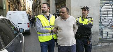 Polic�as, con uno de los detenidos en Barcelona.