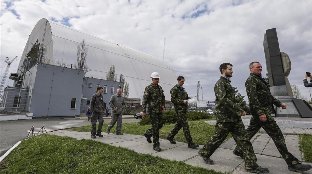 Varios operarios caminan junto a la nueva cubierta protectora de Chernóbil, el 16 de abril.