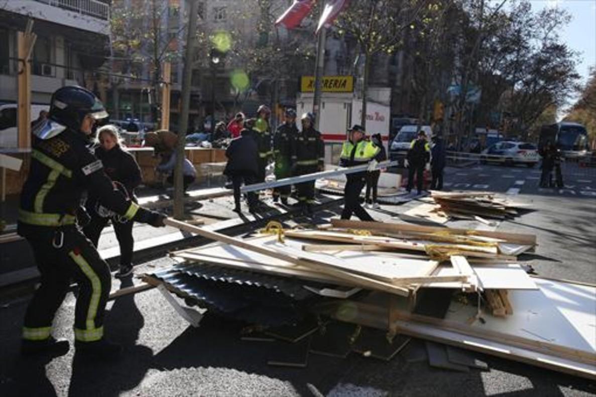 Bomberos y guardias urbanos retiran piezas de uno de los puestos derribados por el viento en la Fira de Reis de la Gran Via de Barcelona, ayer.
