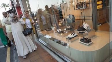 Turistas �rabes pasan por delante de una tienda de lujo en Puerto Ban�s, en Marbella.