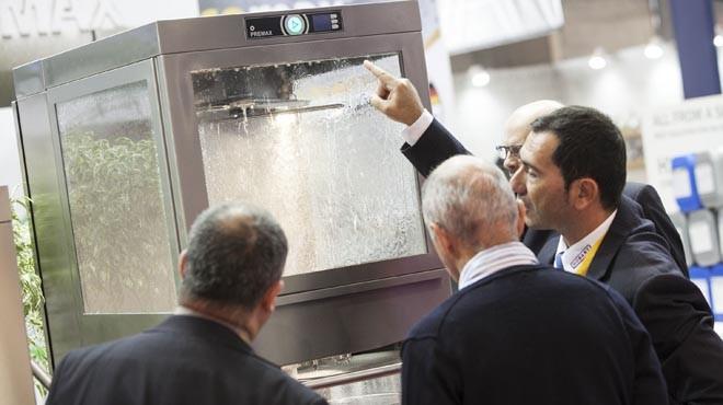 Visitantes en la pasada edición de Hostelco comprueban el funcionamiento de una de las máquinas presentadas