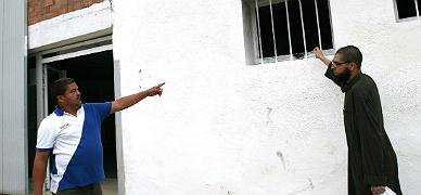 Dos hombres muestran el lugar por el que se ha colado el c�ctel molotov en la mezquita de Tarragona, este viernes.