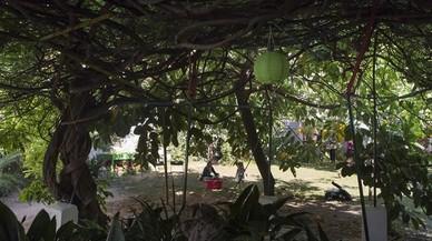 Una madre juega con su hija sobre el c�sped del Jard� del Silenci, instalado en un solar de la calle Encarnaci�.
