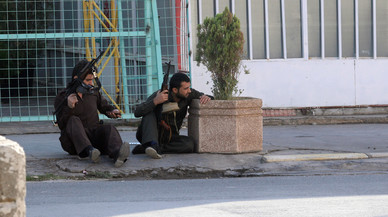 Kurdish security personnel take cover at a site of an attack by Islamic State militants in Kirkuk