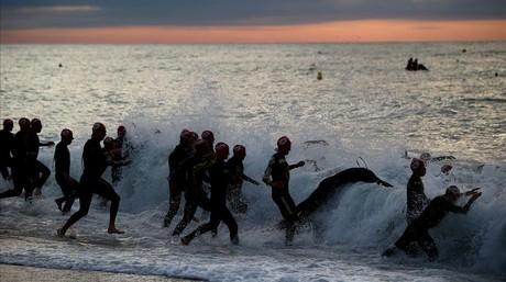 Los participantes se lanzan al agua, con el mar bastante picado, en la playa de Calella en el inicio de la prueba.