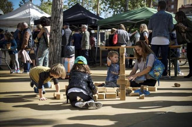 Familias jugando con bloques de madera que llevan Fefe i Companyia para potenciar los juegos de toda la vida, en el Slow Kids del Mercat de la Terra.