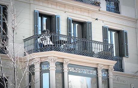 Dos turistas, en el balc�n del albergue que funciona en el n�mero 64 de la Rambla de Catalunya, que ha puesto en pie de guerra a los vecinos.