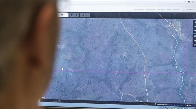 Un voluntario marca la línea de un camino sobre una imagen por satélite de Sierra Leona.