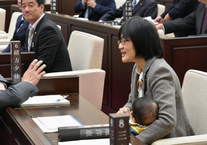 Kumamoto City assembly member Yuka Ogata holds her baby during a session in Kumamoto