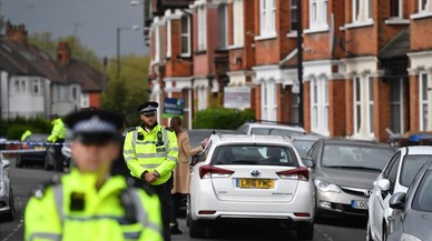 Agentes británicos mantiene un cordón policial en la calle residencial del noroeste de Londres donde tuvo lugar el tiroteo durante una operación antiterrorista, el 28 de abril, en Londres.