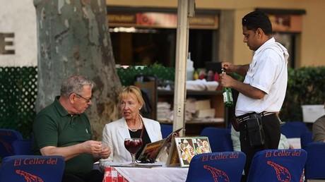 Un camarero atiende a unos clientes en establecimiento de Barcelona.
