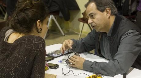 Un técnico ayuda a una usuaria a recuperar un móvil estropeado en el Mobile Social Congress