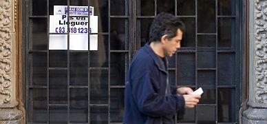Un hombre pasa fente a un cartel en el que se anuncia una vivienda de alquiler, en Barcelona.