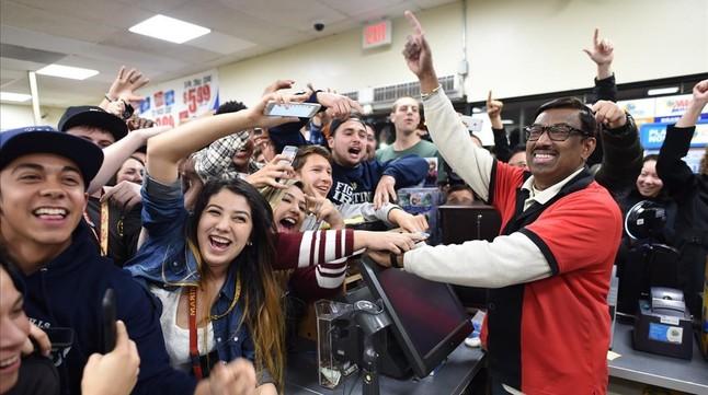 Varios clientes celebran el resultado de la Powerball con el dueño de un establecimiento que vende boletos de lotería, en Chino Falls (California).