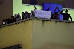Algunos de los amotinados muestran un cartel que pide Libertad, en la azotea del CIE de Aluche.