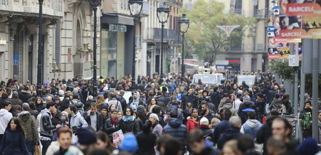 Una multitud de personas pasean en el Portal de l'Àngel de Barcelona.