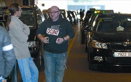 Un taxista exhibe el cartel de 'ocupado' de su vehículo, durante la protesta de ayer en la T-1 del aeropuerto.