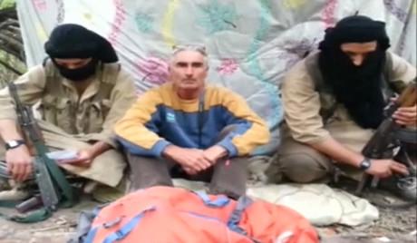 El turista franc�s, que se autoidentifica como Herv� Gourdel, sentado en medio de sus secuestradores, en una imagen de v�deo.