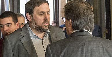 Oriol Junqueras y Artur Mas hablan en los pasillos del Parlament, este jueves.