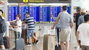 Pasajeros esperando en el aeropuerto de El Prat este martes, donde seguían las colas para pasar el control de seguridad.