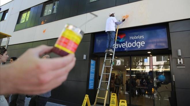 Los operarios del hotel Travelodge limpian las manchas de huevo y de pintura de la fachada.