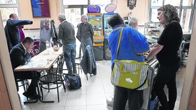 Laura Alb�niz, a la derecha, charla con un cliente en el bar Gelida del Eixample, donde una parte de la clientela son personas mayores del barrio que hace a�os que acuden.