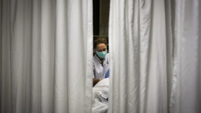 Una enfermera atiende a un paciente en la UCI.