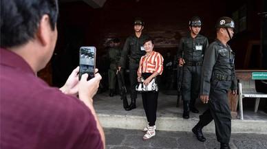 Una turista se fotograf�a con unos soldados en Bangkok, Tailandia.