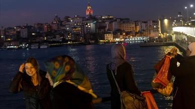 Varias mujeres con pañuelo y sin él fotografían el paisaje de Estambul desde el puente de Galata, el 23 de febrero.