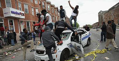 Varios jovenes saltan sobre un coche de la polic�a de Baltimore, este lunes.
