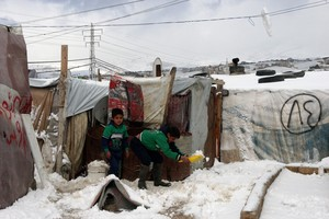Syrian refugees in snow at the Barelias refugee camp