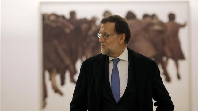 Mariano Rajoy, presidente del Gobierno en funciones junto al cuadro de Juan Genovés, presentado el jueves, después de recoger las credenciales de diputado hoy, en el Congreso de los Diputados.