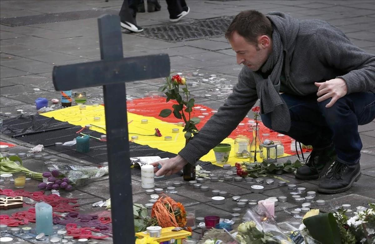 Un hombre deja flores en el tributo a las víctimas de los atentados de Bruselas.