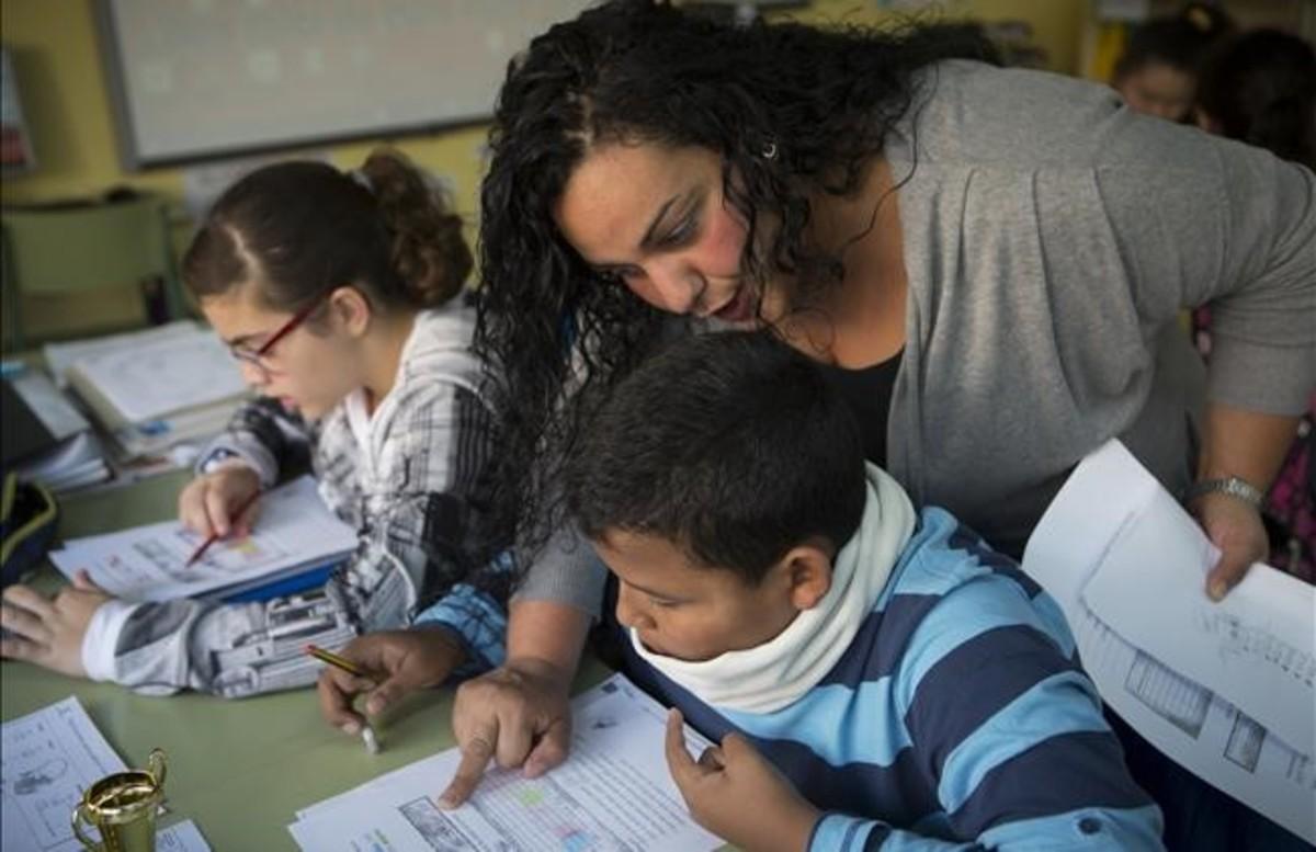 Una madre del colegio Joaquim Ruyra de LHospitalet ayuda como voluntaria a un alumno de sexto de primaria en una clase de Matemáticas.