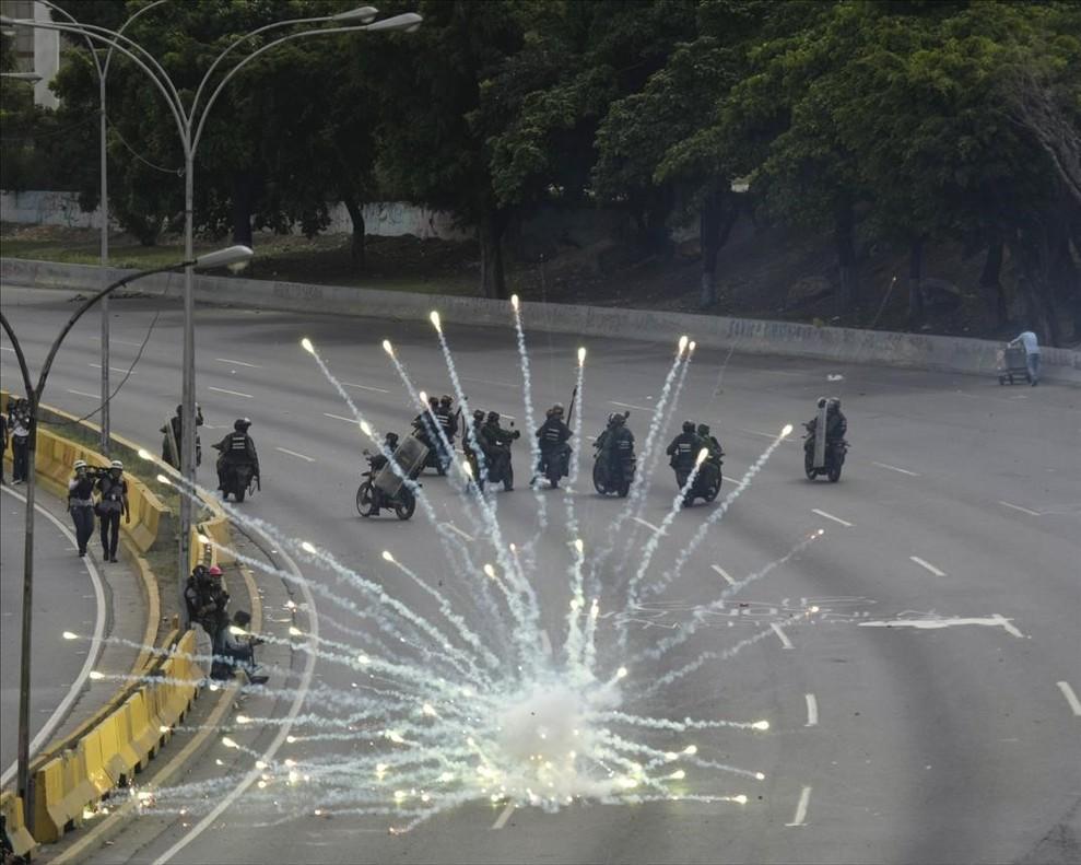 Fuegos artificiales lanzados por manifestantes antigubernamentales explotan junto a lasfuerzas gubernamentales durante los enfrentamientos contra Nicolás Maduro en Caracas, Venezuela.