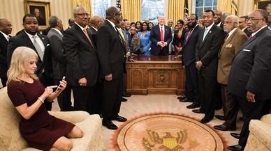 Kellyanne Conway, de rodillas y con zapatos, consulta su móvil mientras Trump y sus invitados posan para la foto oficial.