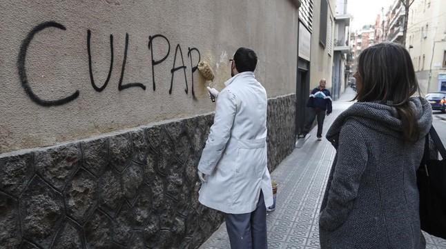 Un trabajador borra una pintada en el muro del colegio de los Maristas de Sants-Les Corts, tras estallar el escándalo de pederastia en el centro.