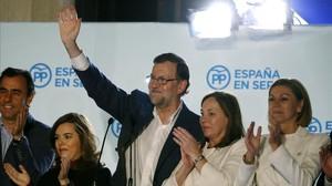 Rajoy y junto a compañeros del partido en el balcón de la sede del PP.